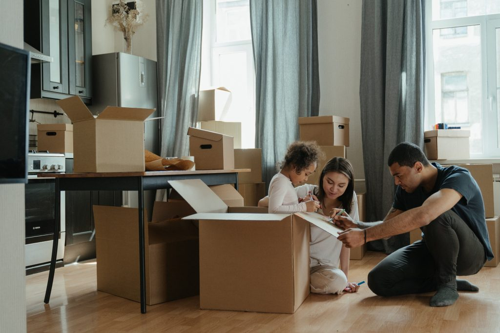 family moving boxes into new house are closing